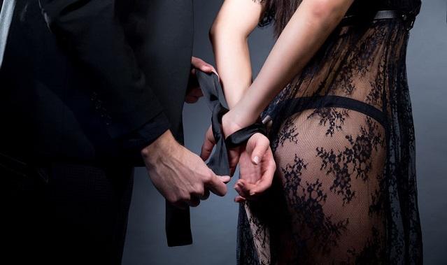 女の手首を縛り付けてる男