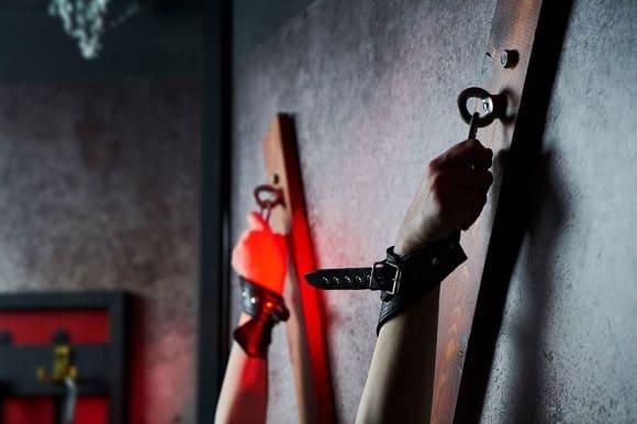 壁の磔に拘束される女