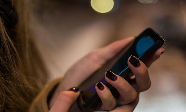 iPhoneをいじってる女